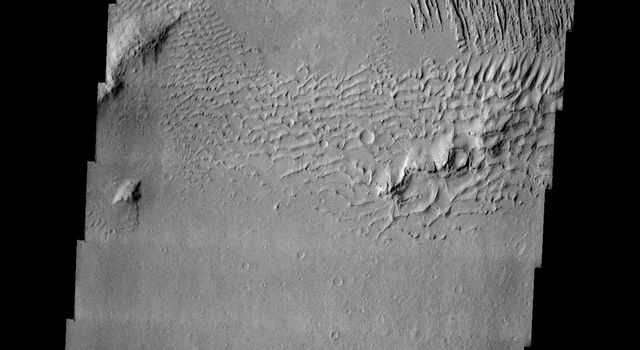 This image released on July 14, 2004 from NASA's 2001 Mars Odyssey shows windstreaks are features caused by the interaction of wind and topographic landforms such as sand dunes with multiple linear ridges. These ridges are yardangs.
