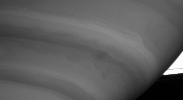 NASA's Cassini spacecraft caught this intriguing view of a dark storm near the limb of Saturn on Sept. 9, 2004.