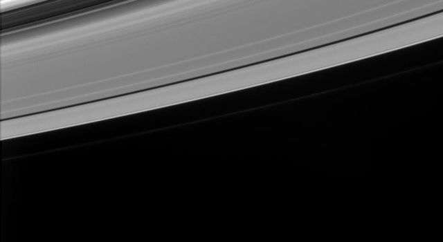 Wave-like patterns in Saturn's rings and a nearly half-full Mimas are caught together in this image from NASA's Cassini spacecraft.