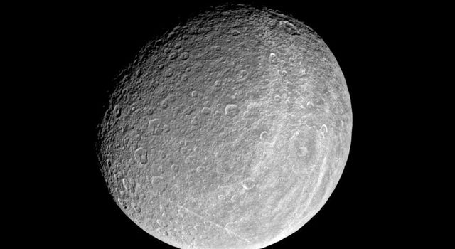 This image from NASA's Cassini spacecraft captures the trailing hemisphere of Saturn's moon Rhea, showing the region's bright wispy markings.