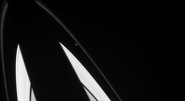 The oddball shapes of Saturn's small ring moons Prometheus and Epimetheus are discernible in this image from NASA's Cassini spacecraft.