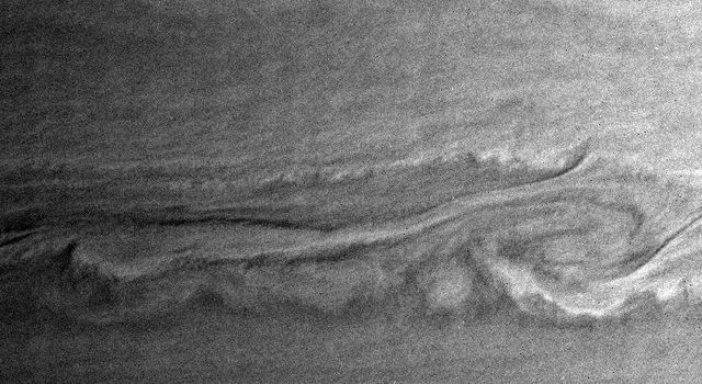 This close-up view of Saturn's turbulent atmosphere captured by NASA's Cassini spacecraft shows what may be two vortices interacting.