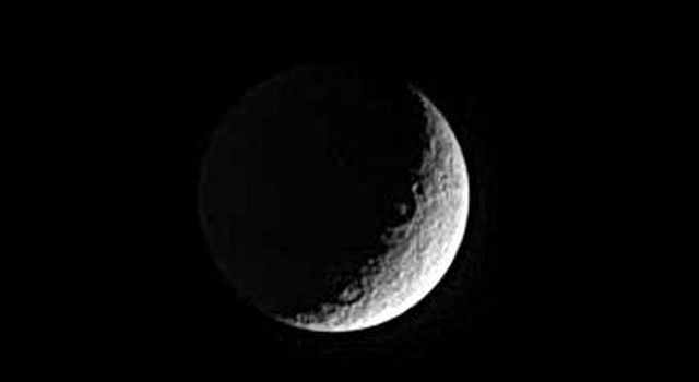 This image captured by NASA's Cassini spacecraft shows two large craters lie along the boundary between day and night on Saturn's moon Rhea.