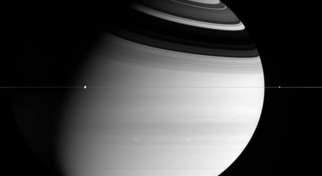 This image captured by NASA's Cassini spacecraft shows Dione and Enceladus orbit the mighty ringed planet Saturn, while two bright storms swirl in the atmosphere below.