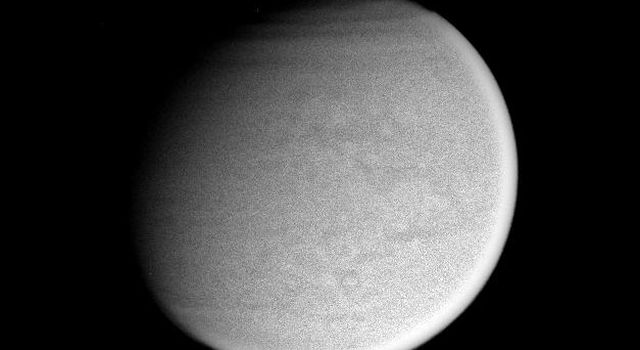 Surface details on Titan are just visible in this image captured by NASA's Cassini spacecraft. Bands in the atmosphere over Titan's extreme northern latitudes.