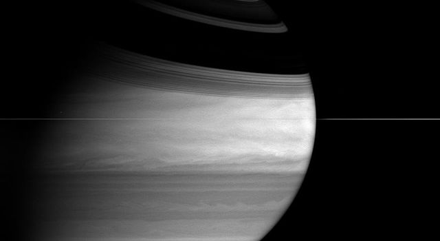 The ringed planet wears a broad grin in this image from NASA's Cassini spacecraft, as the icy rings cast long, sweeping shadows across the northern hemisphere.