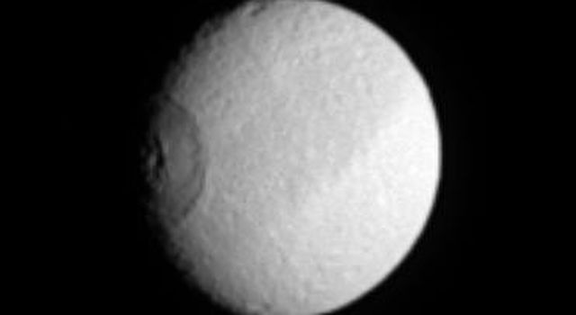 Saturn's moon Tethys turns like a great eye as the enormous crater Odysseus (450 kilometers or 280 miles across) rotates into NASA's Cassini spacecraft's view.