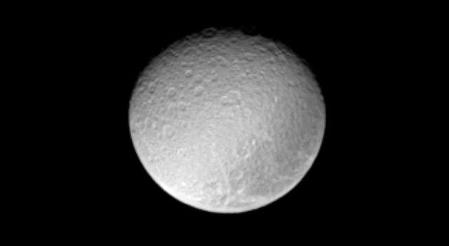 The ancient and battered surface of Saturn's moon Rhea shows a notable dark swath of territory near the eastern limb in this image from NASA's Cassini spacecraft.