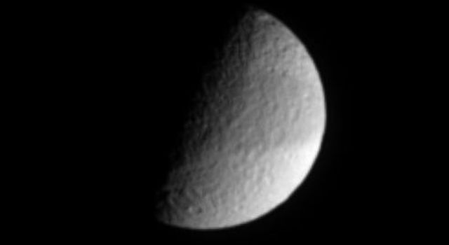 In this infrared view from NASA's Cassini spacecraft, Saturn's cratered moon Tethys shows a faint, dark band across its equatorial region.