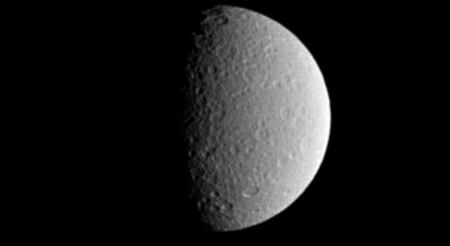 This image captured by NASA's Cassini spacecraft shows the cratered surface of Saturn's moon Rhea, with impact craters near the terminator thrown into sharp relief.