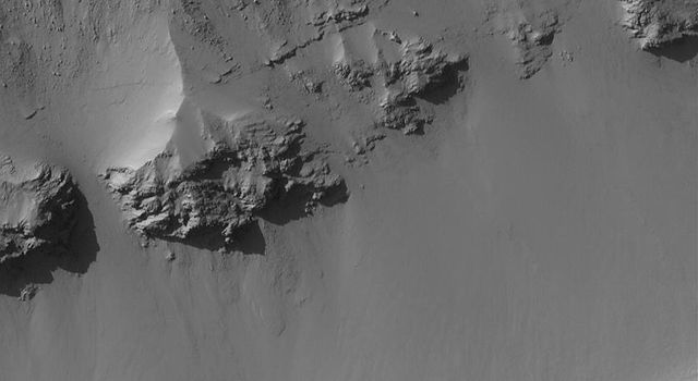 NASA's Mars Global Surveyor shows the layered rocks and boulders exposed on the wall of a trough in the Terra Sirenum region of Mars.