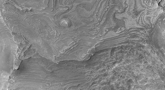 NASA's Mars Global Surveyor shows layered, sedimentary rock outcrops in southwestern Melas Chasma, one of the troughs of the vast Valles Marineris system on Mars.