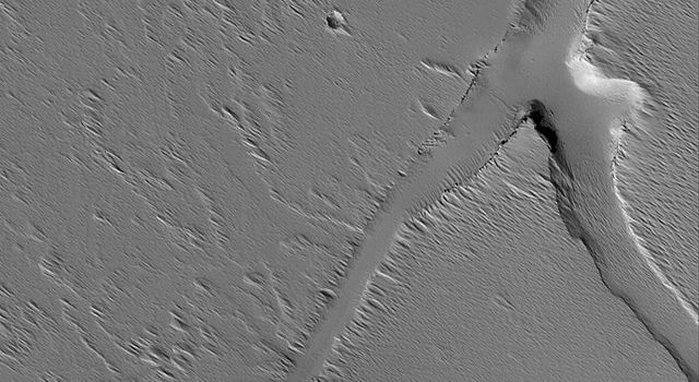 NASA's Mars Global Surveyor shows troughs and a pit, possibly formed by collapse, on the volcanic plains south of the large volcano, Ascraeus Mons on Mars. Wind-eroded debris mantles the scene and partly fills the depressions.