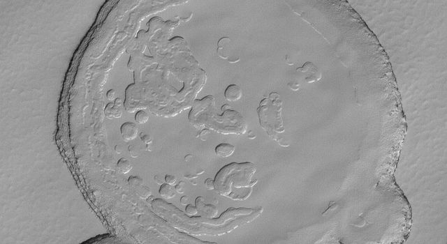 NASA's Mars Global Surveyor shows mesa tops and depressions formed in layered carbon dioxide ice in Mars' south polar residual cap.