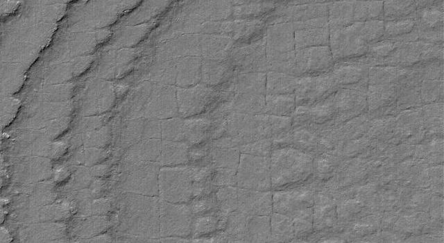 NASA's Mars Global Surveyor shows layers broken-up by processes that form nearly square polygonal cracks and textures in the south polar region of Mars.