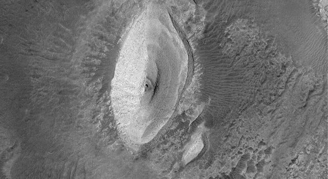 NASA's Mars Global Surveyor shows a light-toned butte composed of layered, sedimentary rock in the Iani Chaos region of Mars.