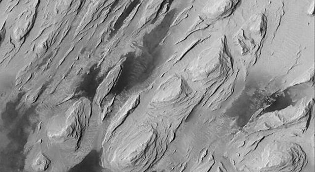 NASA's Mars Global Surveyor shows the effects of severe wind erosion of layered sedimentary rock in the Aeolis region of Mars. The sharp ridges formed by wind movement are known as yardangs.