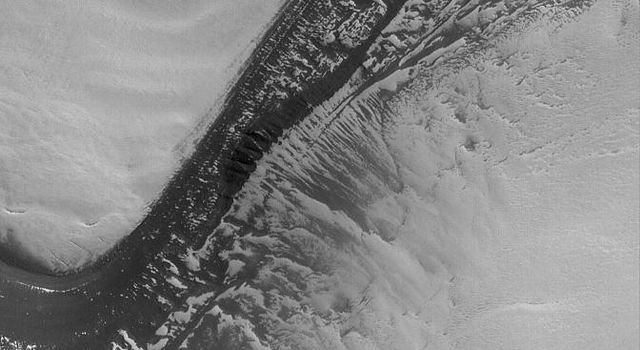 NASA's Mars Global Surveyor shows a dark, layered scarp in the martian north polar region. All of the light-toned surfaces are covered by frost left over from the previous winter.