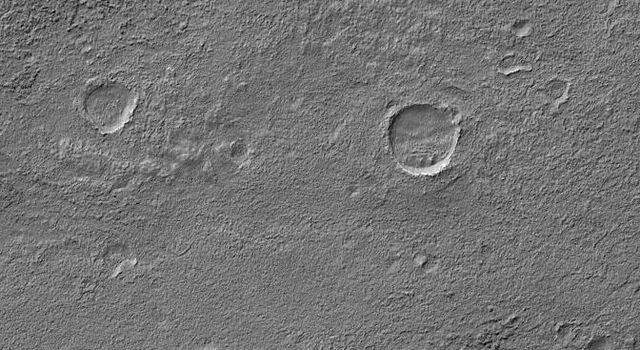 NASA's Mars Global Surveyor shows a crater near the rim of Kaiser Crater, in Noachis Terra on Mars, with several layers of eroded material. This crater, and probably all of its degraded neighbors, was once filled and buried, and was later exhumed.