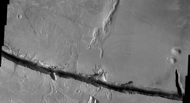 This image released on August 30, 2004 from NASA's 2001 Mars Odyssey shows Cerberus Fossae on Mars, comprised of two east/west oriented linear depressions. Fossae is a long, narrow, shallow depression.