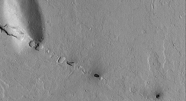 NASA's Mars Global Surveyor shows a small line of collapsed pits that follow the trend of the regional Cerberus Fossae troughs on Mars.