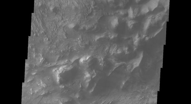 This image released on Sept 21, 2004 from NASA's 2001 Mars Odyssey shows Candor Chasma's northern rim on Mars. Just below the canyon wall is debris material that once formed part of the canyon wall.