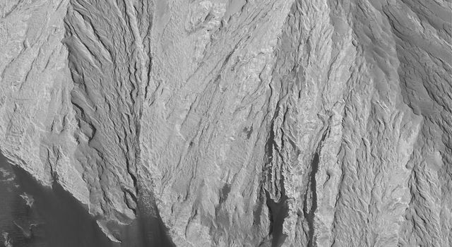 NASA's Mars Global Surveyor shows a thick, massive outcrop of light-toned rock exposed within eastern Candor Chasma, part of the vast Valles Marineris trough system on Mars. Dark, windblown sand has banked against the lower outcrop slopes.