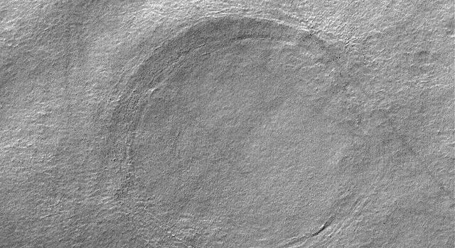NASA's Mars Global Surveyor shows a circular feature buried in an impact crater in southern Noachis Terra on Mars.