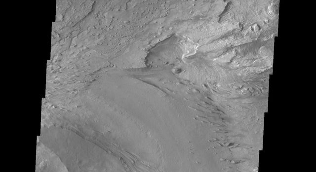 This image released on Oct 6, 2004 from NASA's 2001 Mars Odyssey shows an area on Mars in Candor Chasma. Layered surfaces and wind etched surfaces are present in this area.