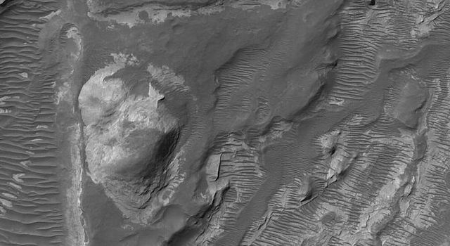 NASA's Mars Global Surveyor shows light-toned, layered rock outcrops in a pitted and eroded region just northeast of Hellas Planitia on Mars. The light-toned materials are most likely sedimentary rocks deposited early in martian history.