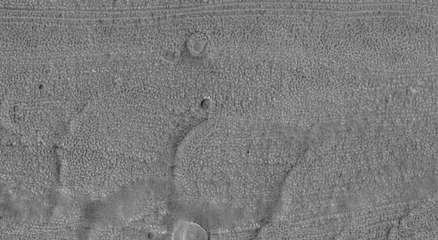 NASA's Mars Global Surveyor shows a fretted terrain valley floor with its characteristic lineated and finely-pitted texture. Four circular features are suspected to be the locations of meteor impact craters that have been largely eroded away.
