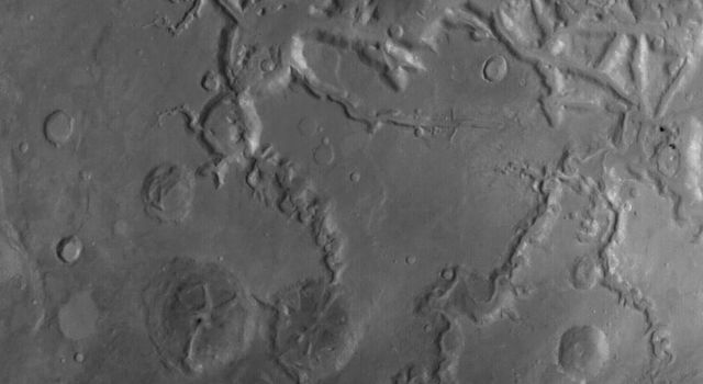 NASA's Mars Global Surveyor shows a portion of the fretted terrain north of eastern Arabia Terra on Mars. The long valley that runs diagonally is called Auqakuh Vallis.