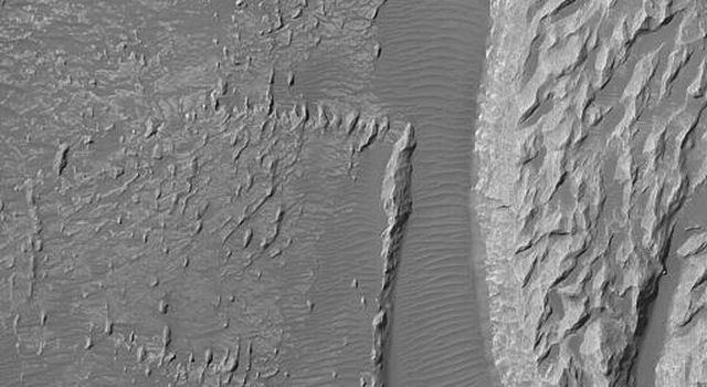 NASA's Mars Global Surveyor shows light-toned rock outcrops, possibly sedimentary rocks, in the Arsinoes Chaos region east of the Valles Marineris trough system. These rocky materials were once below the martian surface.