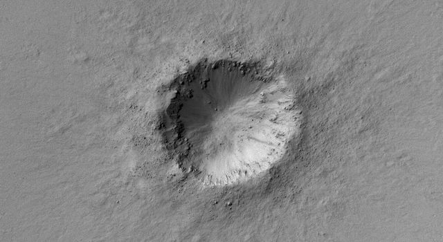 NASA's Mars Global Surveyor shows a small meteor impact crater with bouldery ejecta in the Arabia Terra region of Mars.