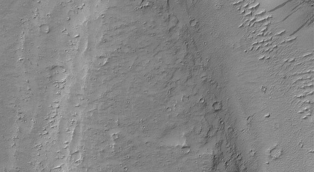 NASA's Mars Global Surveyor shows a streamlined landform in the Mangala Valles region of Mars. An ancient catastrophic flood, probably consisting of water and debris, ran northward.