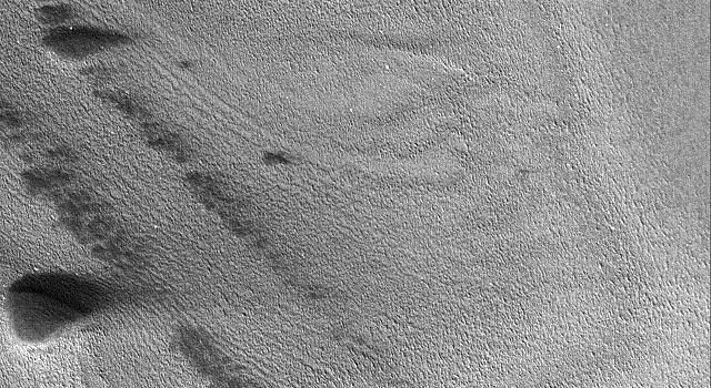 NASA's Mars Global Surveyor shows banded terrain of the north polar region of Mars. The bands are exposures of layered material, possibly composed of dust and ice.