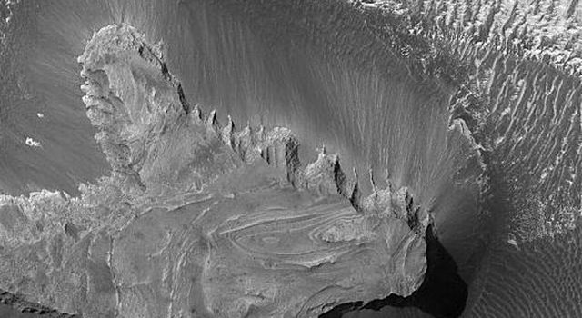 NASA's Mars Global Surveyor shows light-toned, layered outcrops of sedimentary rock exposed at the top of a small mesa in northern west Candor Chasma of the Valles Marineris trough system on Mars. Large, dark, windblown ripples cover the plains.