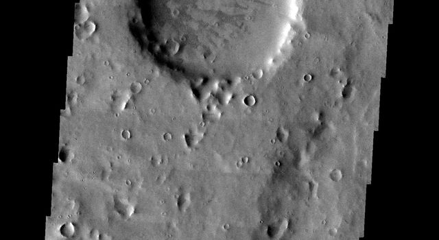 This image from NASA's Mars Odyssey shows a large crater on Mars, older than all the smaller craters around it from the region near Naktong Vallis. The crater no longer has any visible rim or ejecta, and is simply a circular smooth floored basin.