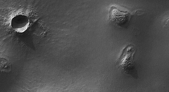 NASA's Mars Global Surveyor shows buttes, craters, and exhuming impact craters in central Argyre Planitia on Mars.