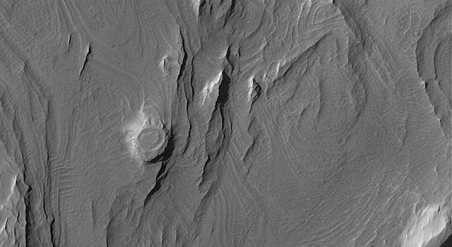 NASA's Mars Global Surveyor shows layered rocks, in some areas eroded by wind to form yardangs, in eastern Candor Chasma, one of the troughs of the Valles Marineris system on Mars.
