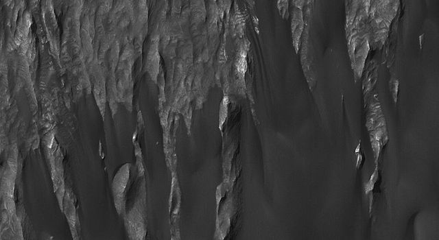 NASA's Mars Global Surveyor shows wind-eroded remnants of sedimentary rock outcrops in Ganges Chasma, one of the troughs of the Valles Marineris system on Mars. A thick accumulation of dark, windblown sand is present.