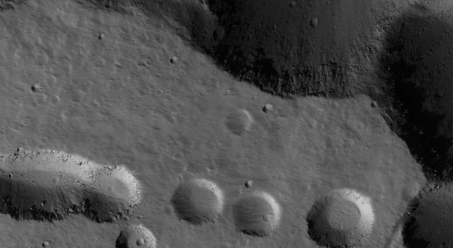 NASA's Mars Global Surveyor shows collapse pits on the northern flank of the giant Tharsis shield volcano, Ascraeus Mons on Mars. Large, dark boulders occur on the floors of some of the pits.