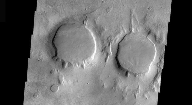 This image is part of THEMIS art month, taken by NASA's Mars Odyssey featuring a portion of Mars' landscape looking like a pair of eyes.