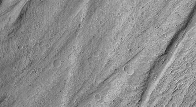 NASA's Mars Global Surveyor shows portions of the lobes of several landslide deposits in Ganges Chasma on Mars. Dark material near the bottom of the image is windblown sand.