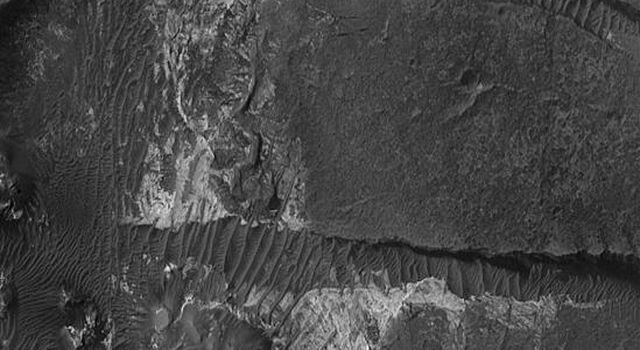 NASA's Mars Global Surveyor shows light-toned sedimentary rock outcrops and large dark-toned, windblown ripples in Aram Chaos on Mars.
