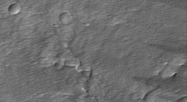 NASA's Mars Global Surveyor shows wind streaks and a thick mantling of dust in the summit region of the martian volcano, Pavonis Mons. Several very small, sharp impact craters are present.