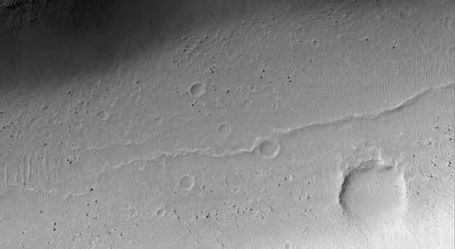 NASA's Mars Global Surveyor shows boulders on the floor of a wide trough in Memnonia Fossae on Mars.