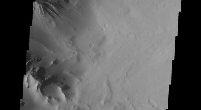 This image taken by NASA's Mars Odyssey shows part of the caldera of Tharsis Tholus on Mars; fractures are visible in the cliff wall it is possible to see that the fractures dip to the north.
