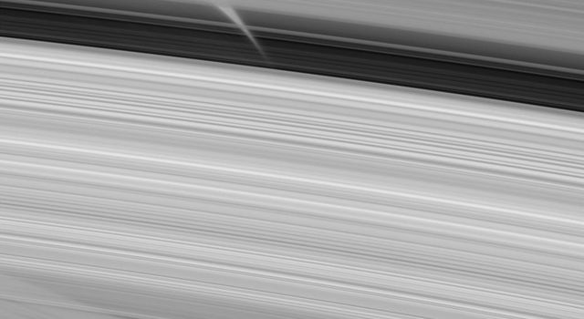 This close-up image from NASA's Cassini spacecraft peers directly through regions of the A, B and C rings (from top to bottom here) to glimpse shadows of the very same rings cast upon the planet's atmosphere.