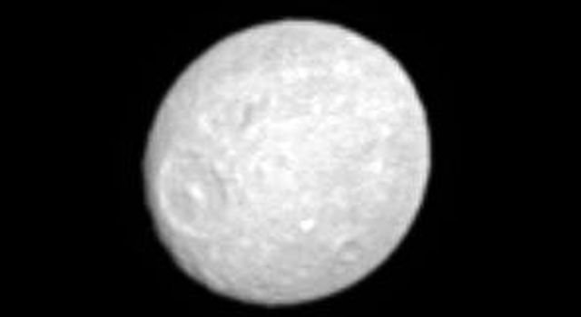 Saturn's moon Mimas, whose low density suggests that it is primarily composed of ice, has a flattened or oblate shape reminiscent of Saturn's. This image was taken in visible light with NASA's Cassini spacecraft's narrow-angle camera on May 20, 2005.